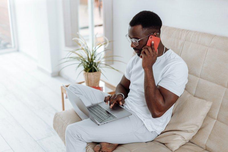 Hombre que trabaja en casa sentado en el sofá con su laptop y su teléfono móvil