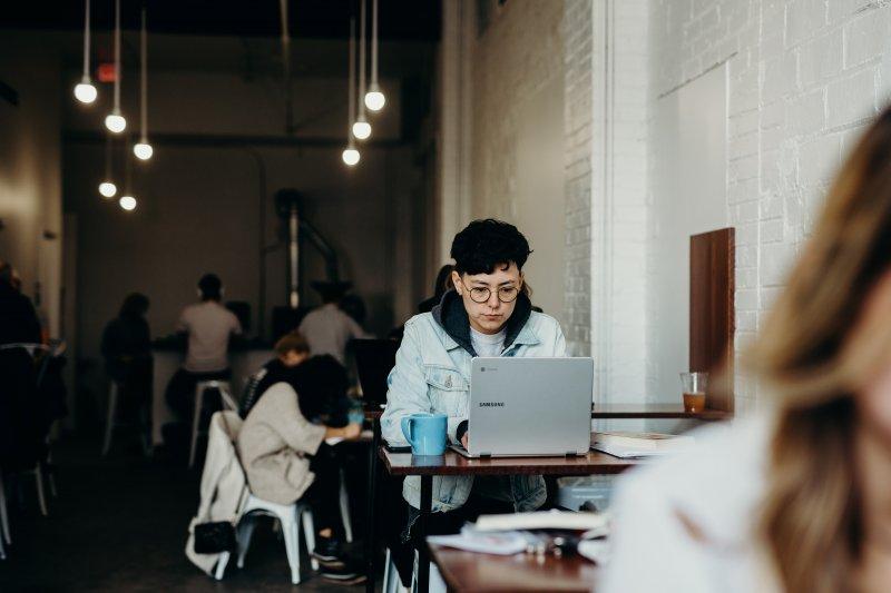 Una mujer joven trabaja en remoto con su ordenador portátil en una cafetería