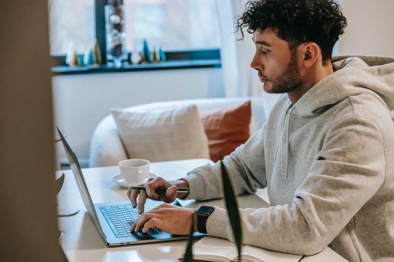 Un hombre está en su casa y busca trabajo con el ordenador portátil