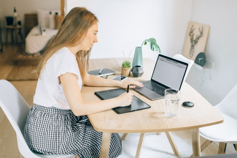 Una mujer trabaja en su casa con el ordenador y un lápiz digital