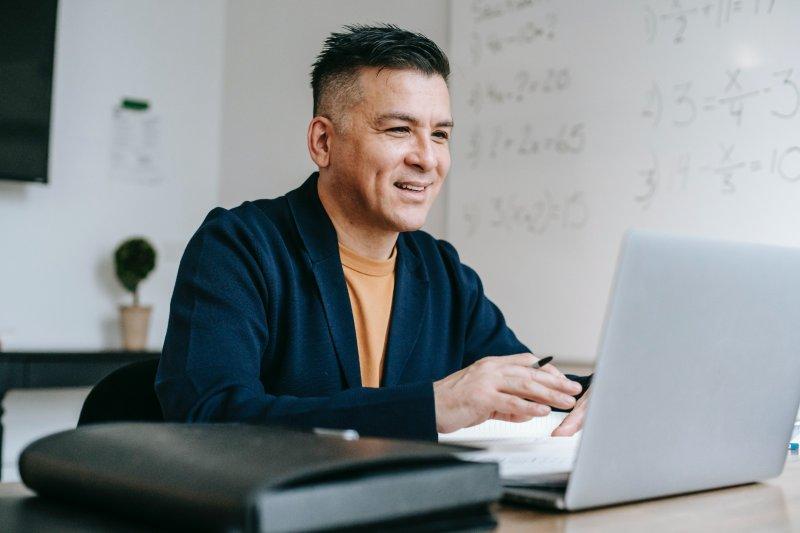 Un hombre realiza una videoconferencia con su ordenador portátil y toma apuntes en una libreta