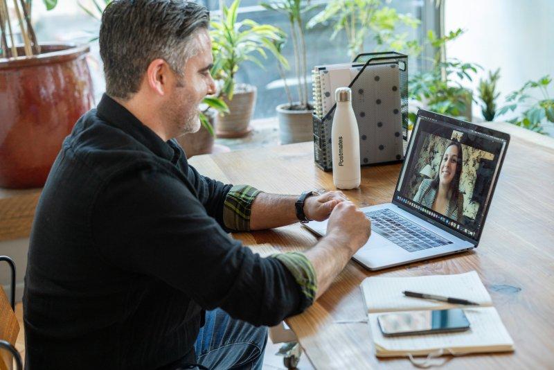 Un hombre realiza una videoconferencia con una compañera de trabajo
