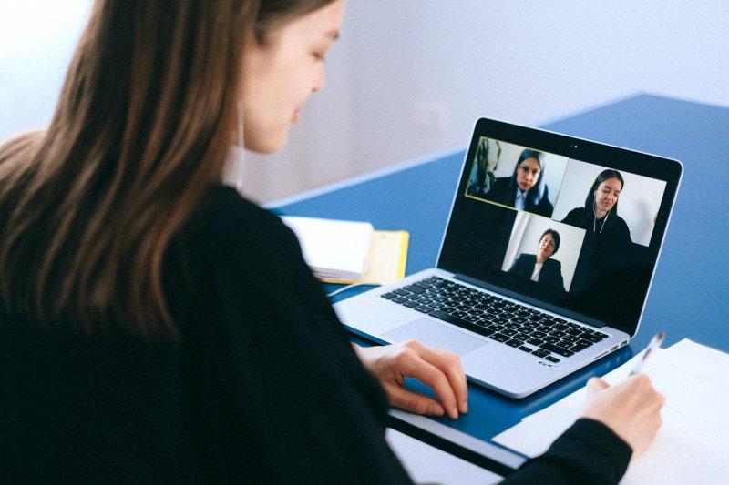 Una chica escribe en una hoja mientras participa desde su casa en una videollamada con compañeras de trabajo.