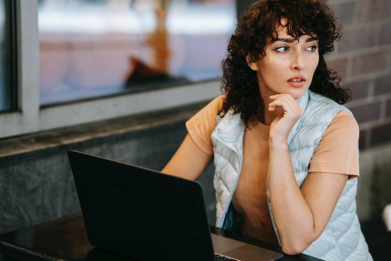 Mujer gira la vista a un lado para no sufrir fatiga visual con la pantalla del ordenador